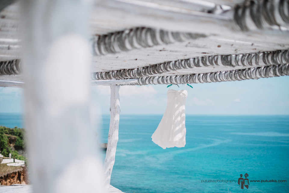 Camille's wedding dress hanging with blue sea in the background