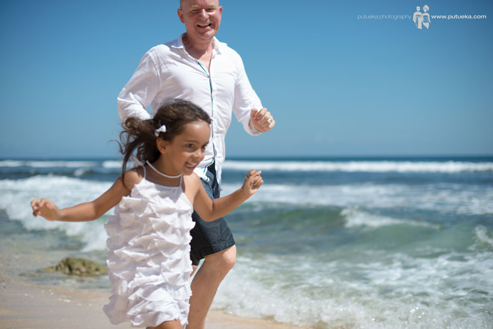 Running along the shoreline with big smile and laugh on family photography session