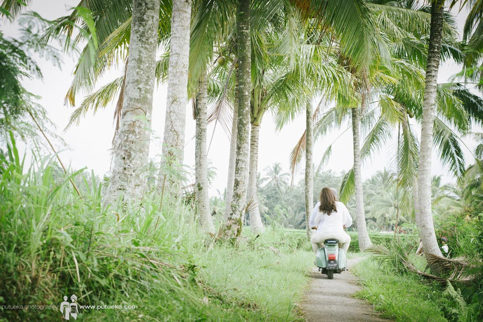 Riding scooter under coconut trees on family vacation photography session in Ubud Bali
