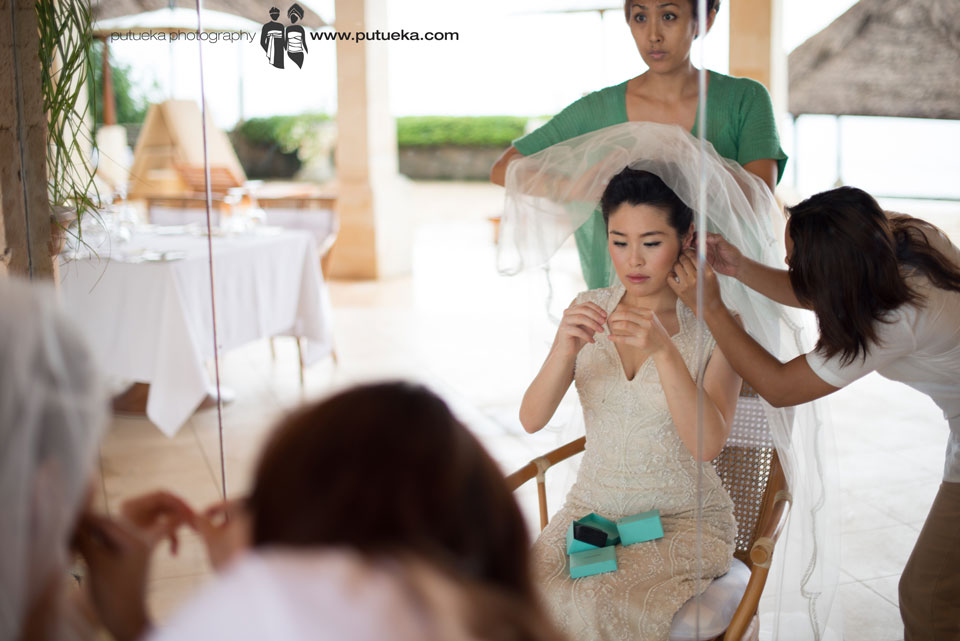 Assistant of makeup artist help Jessie to wear earing