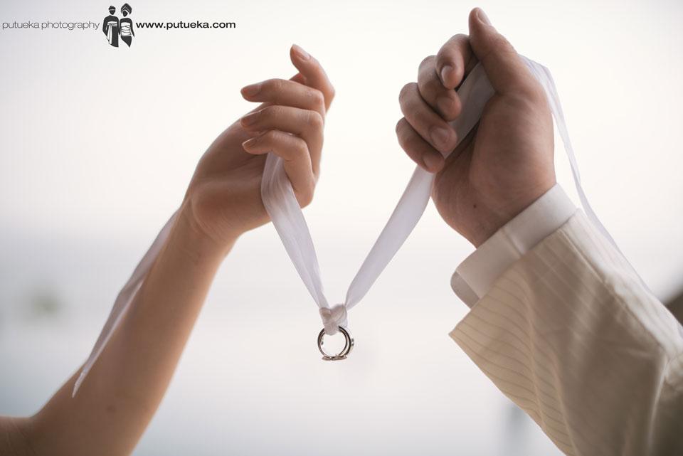 Jessie and Boris wedding rings hanging between their hands