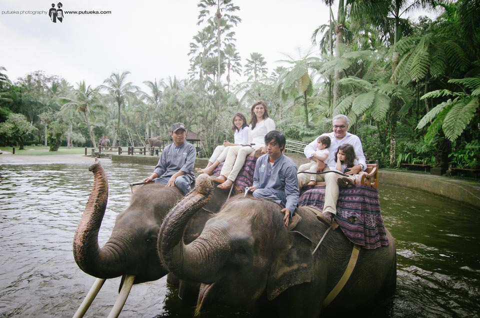 Whole family riding elephants in the middle of the pond