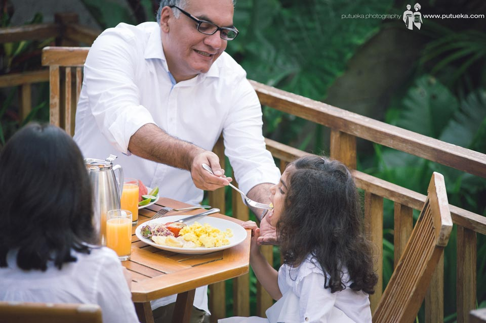 Happy father feeding his daughter in the morning
