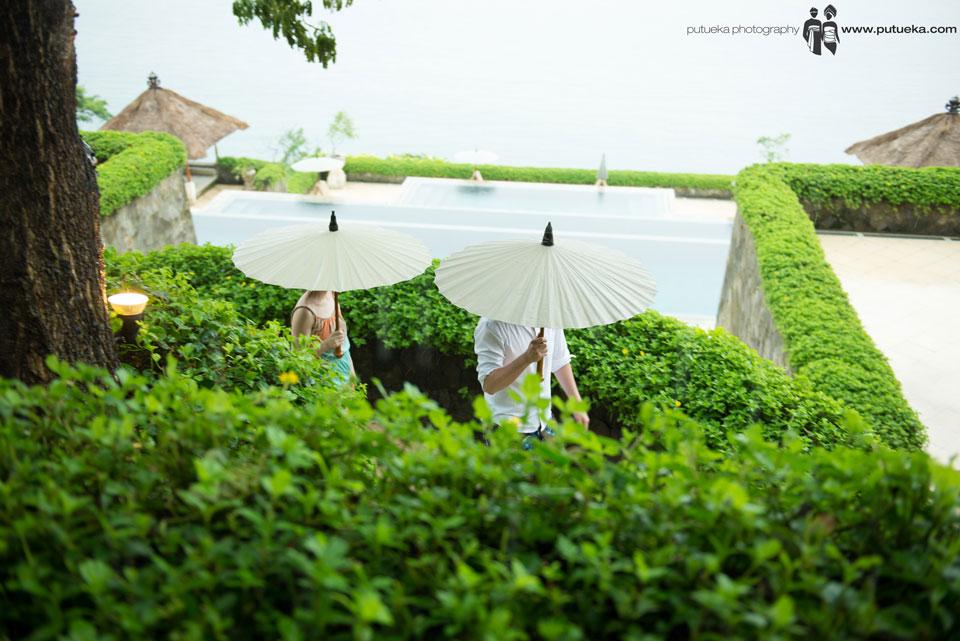 Boris and Jessie walking using umbrella before their wedding at Amankila Bali