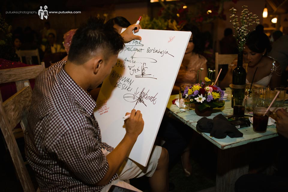 Guest writing congratulation on canvas