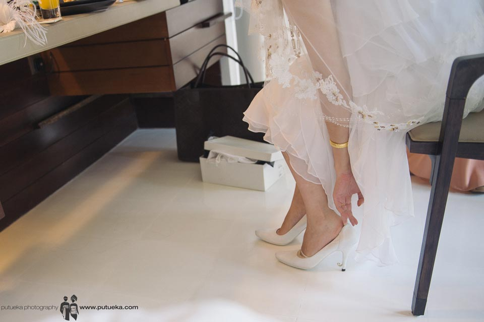 Bride wearing her wedding shoes