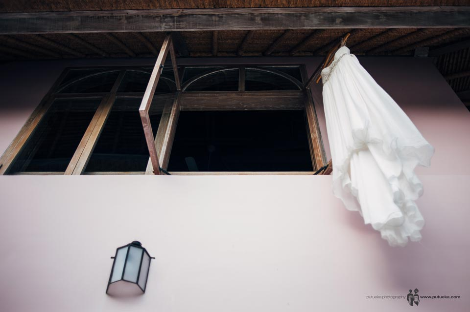 Ayu wedding dress hanging outside the window of Hacienda villa no 5 master bedroom