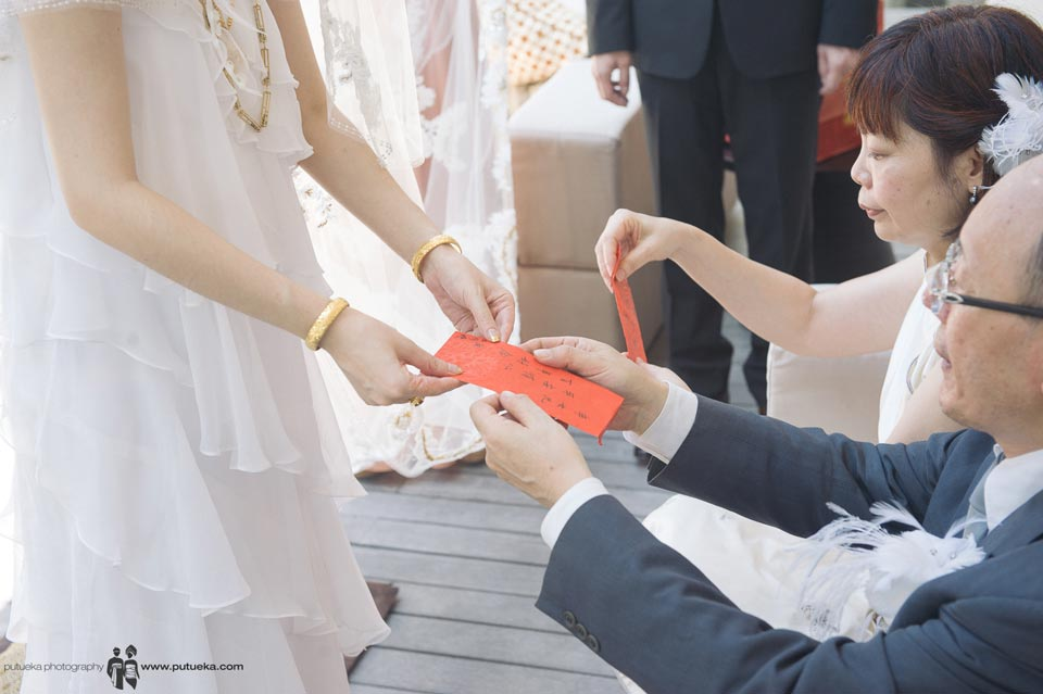 Father and mother give red envelope to bride
