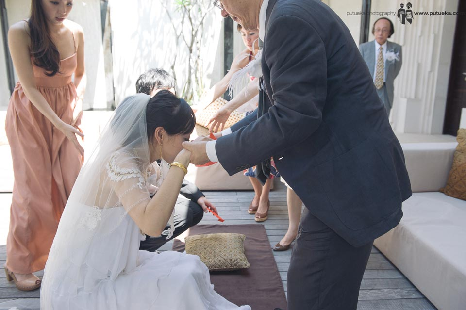 Parent help bride and groom to stand