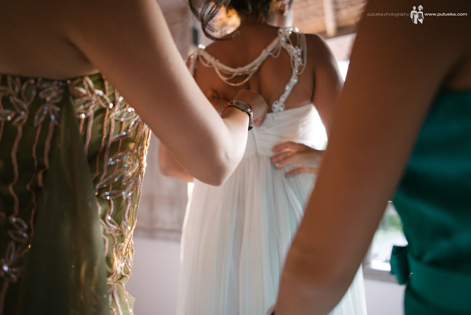 Bridesmaid fasten the wedding dress zipper