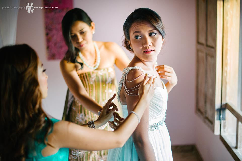 Bridesmaid help ayu to wear the wedding dress