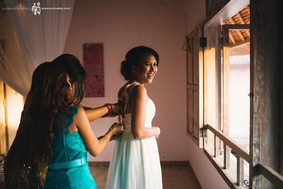Bridesmaid help Ayu to fasten the wedding dress zipper