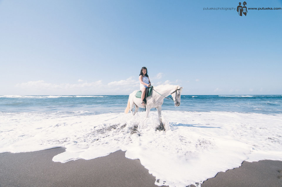 Bali family photography session with horse and wave splash on the beach