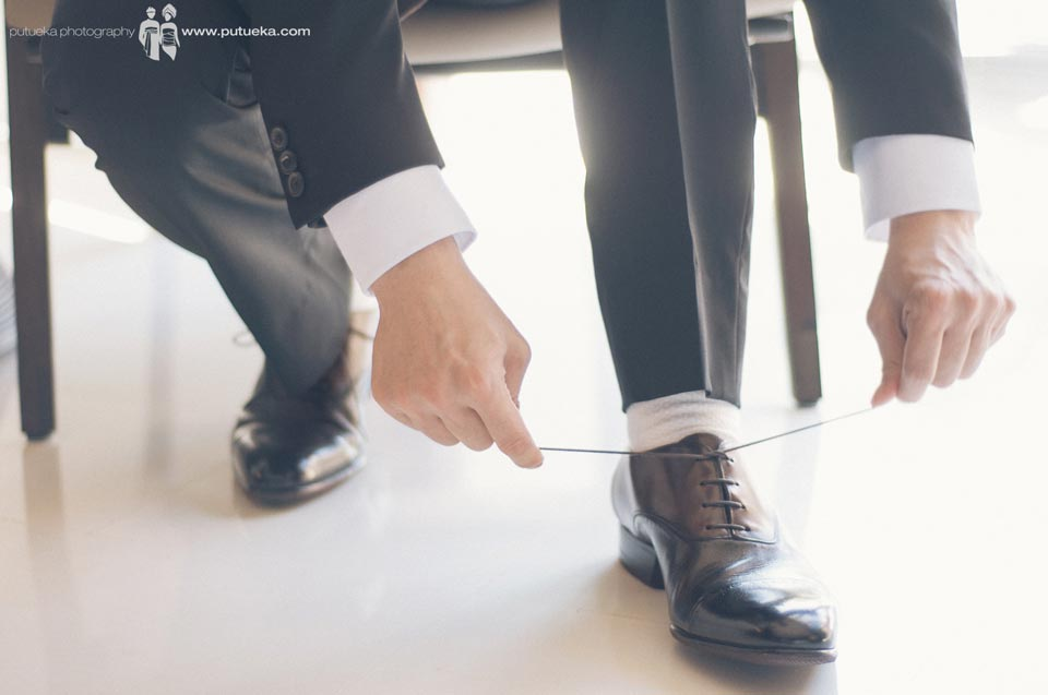 Groom tying his wedding shoelaces