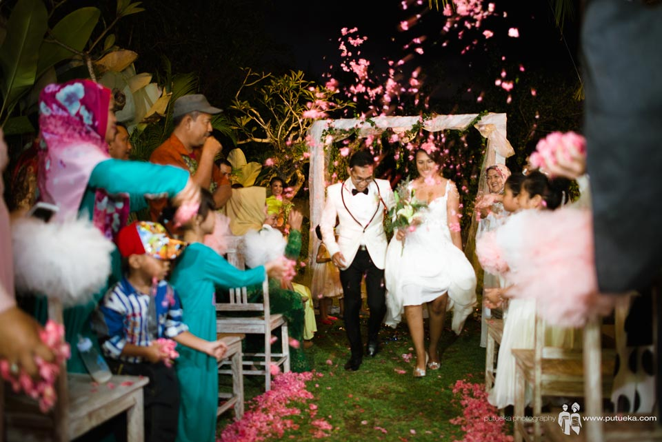 Brides and groom walking under flower shower