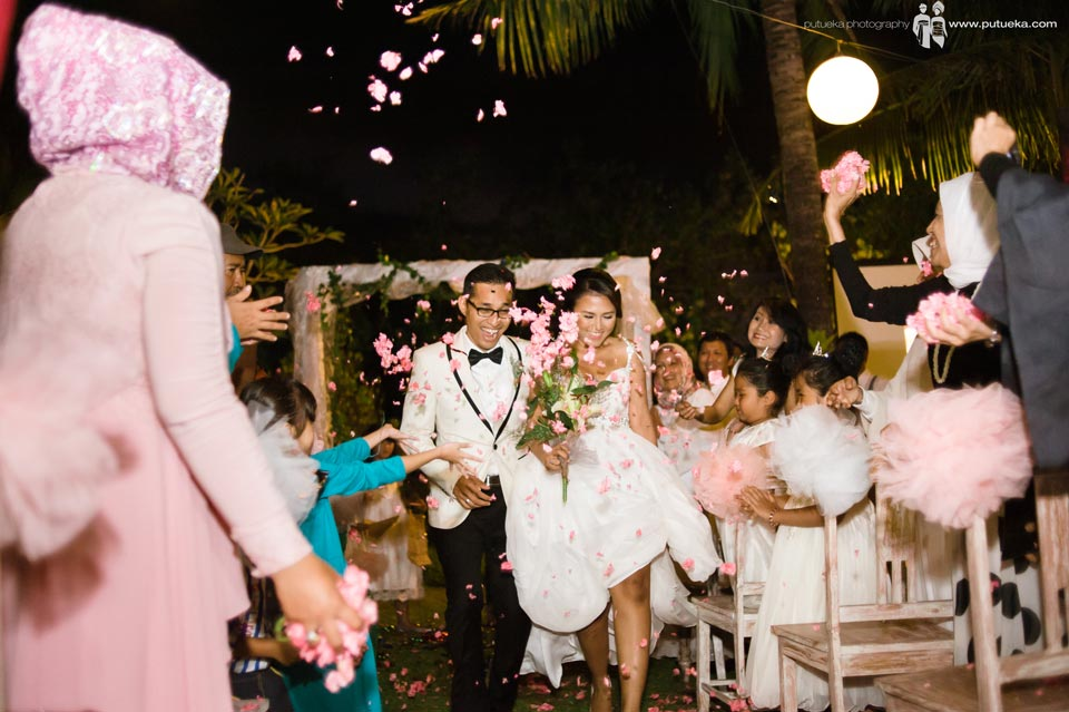 Brides and groom walking under flower shower from attendace