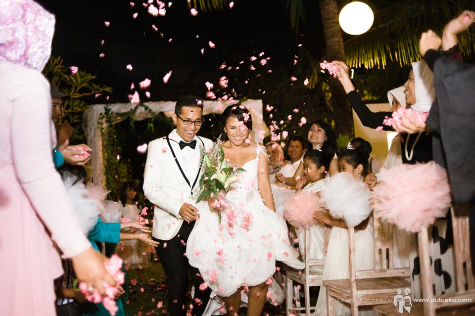 Ayu and Hakim walking under flower shower with smile on their faces