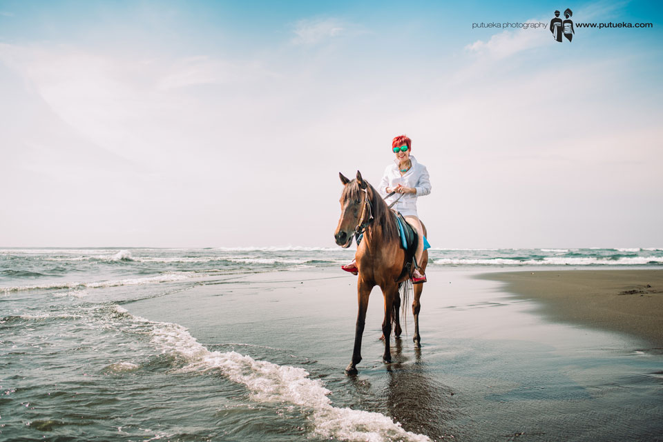 Annie riding the horse on the beach in the morning
