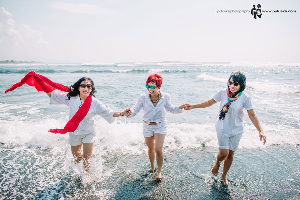 Annie and friends lauhing happily when their feet splash by the wave